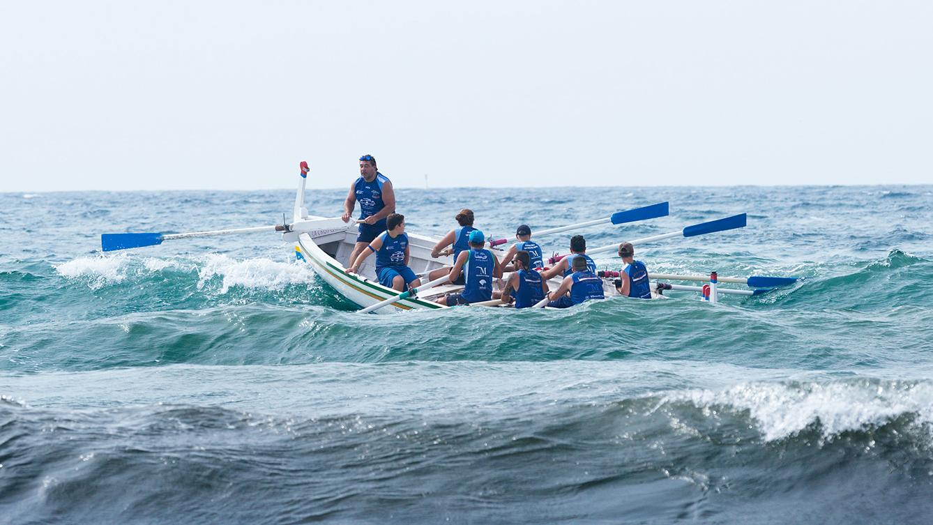 A photo of a rowing team on rough water
