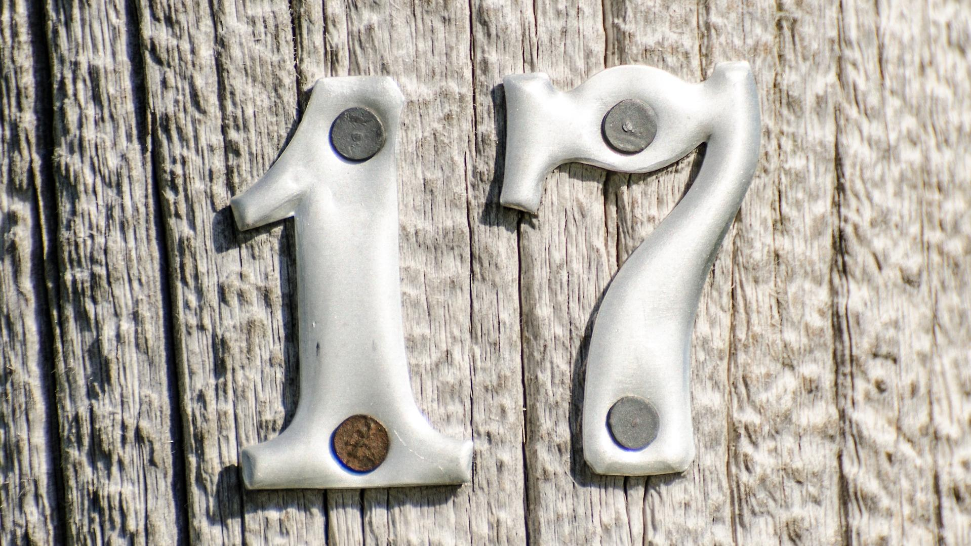 metallic number seventeen nailed to a wood surface
