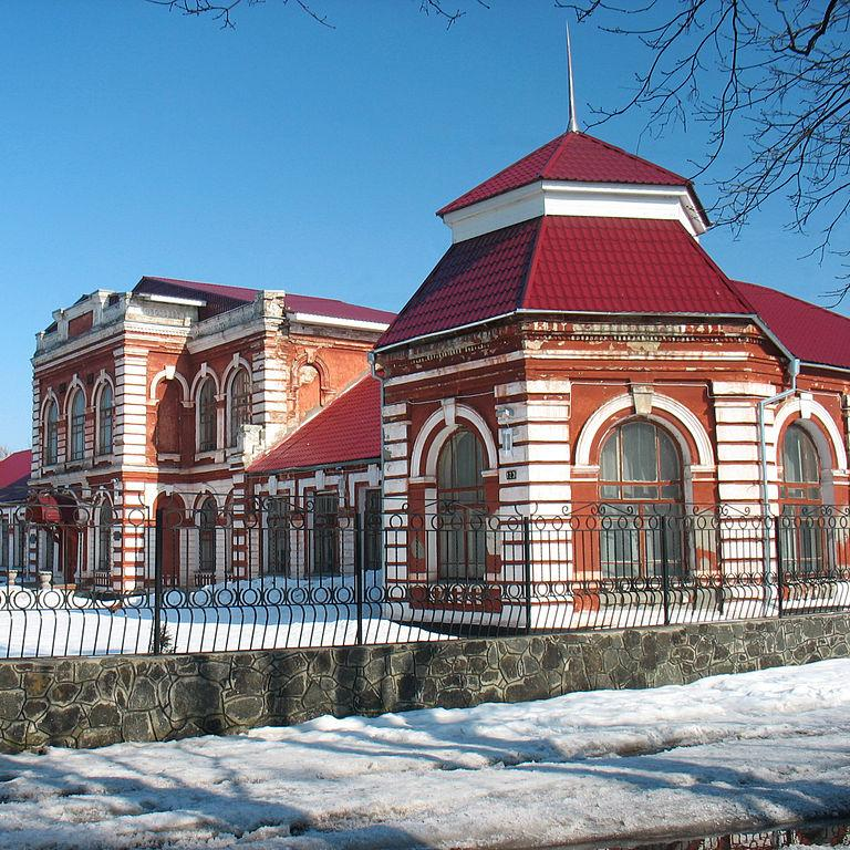 A photograph of a red and white brick romanesque women's gymnasium in Smila, Ukraine.